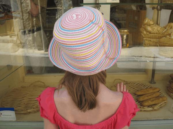 france-menerbes-girl peering in window of bakery