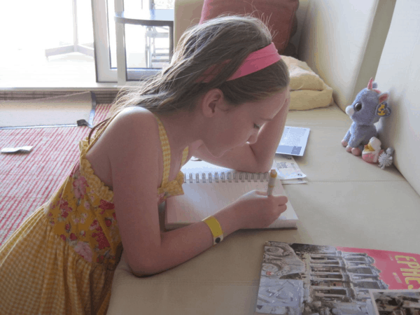 Child writing in travel journal