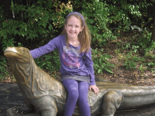 girl on komodo dragon statue at Toronto Zoo