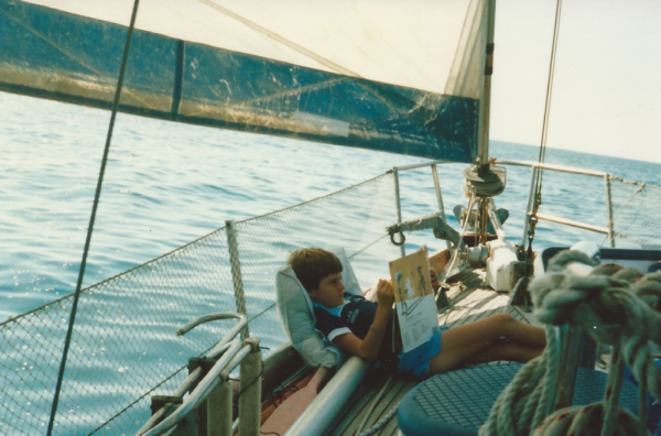 boy on sailboat reading book