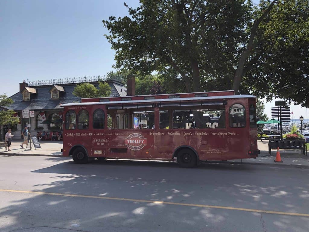 red trolley bus parked on street in Kingston