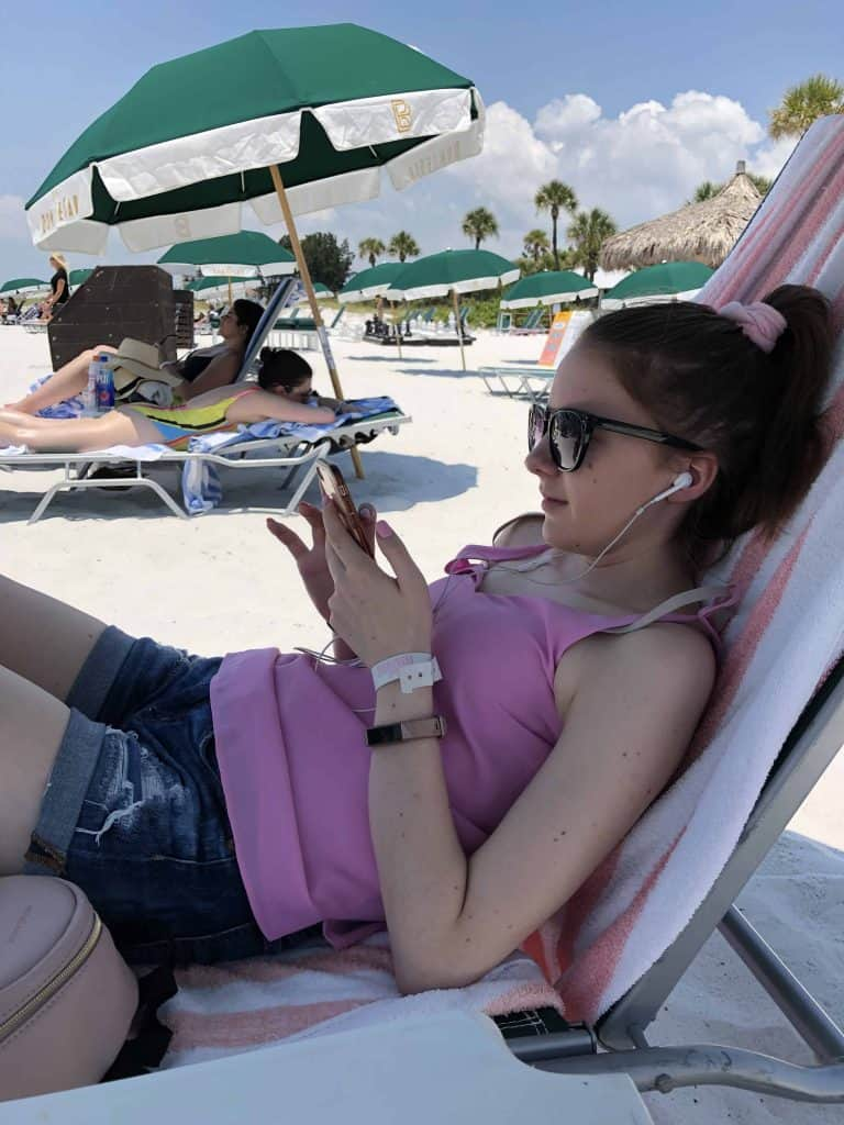 young woman with headphones and phone sitting on beach chair