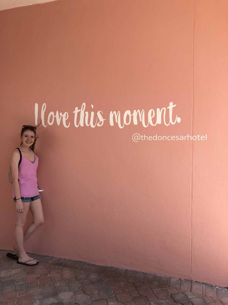 young woman pink top in front of pink wall with words I love this moment on wall