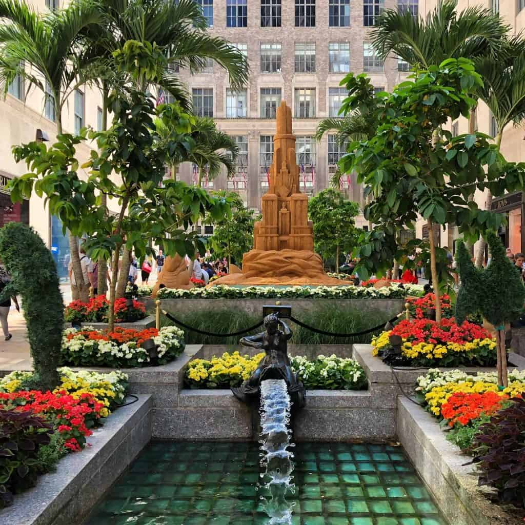 tropical garden with sand castle and water feature in city