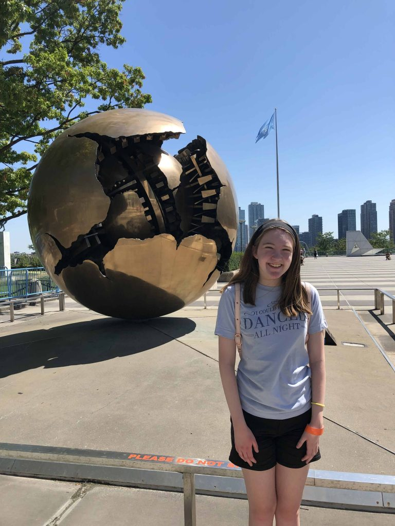 teen in front of round sculpture with UN flag in background