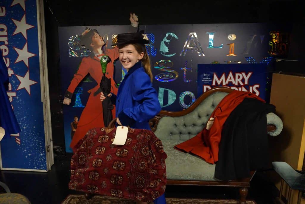 teen dressed as mary poppins with props from broadway musical