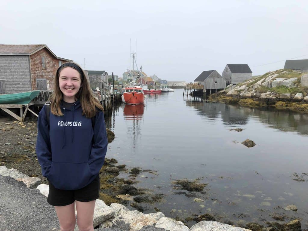 peggy's cove nova scotia-teen girl standing by water with boats and weathered buildings