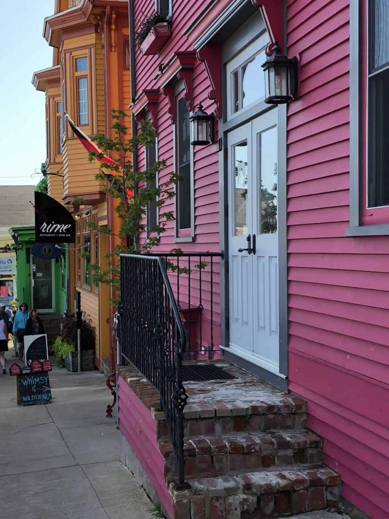 pink green and orange building fronts on street