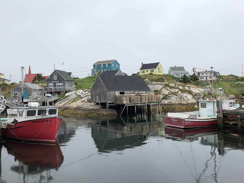 nova scotia lighthouse route-peggy's cove-red and white boats and colourful buildings on rocky shore
