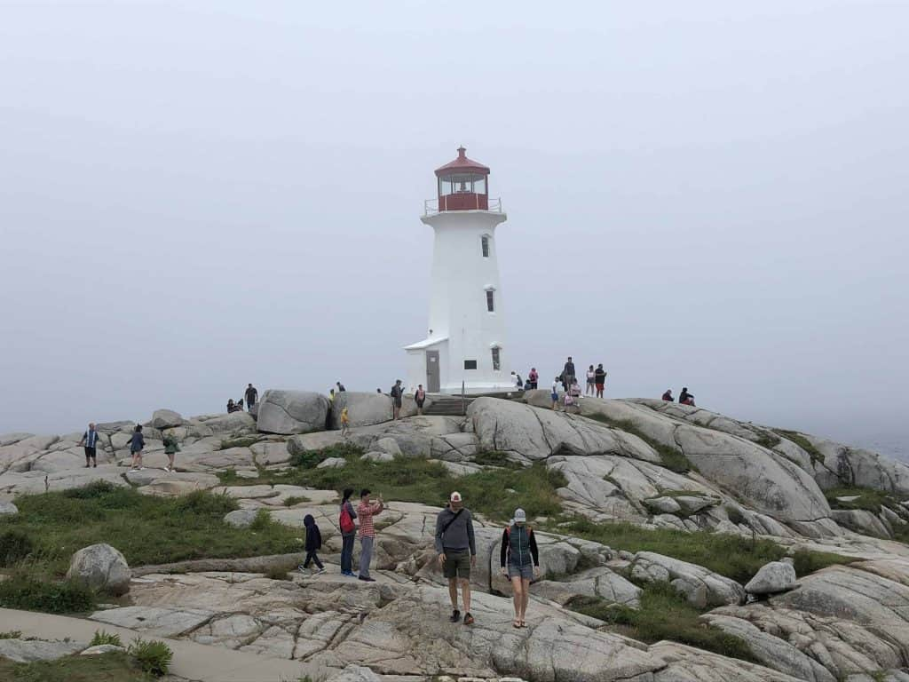 nova scotia lighthouse route-peggy's cove-red and white lighthouse on rocks with people around