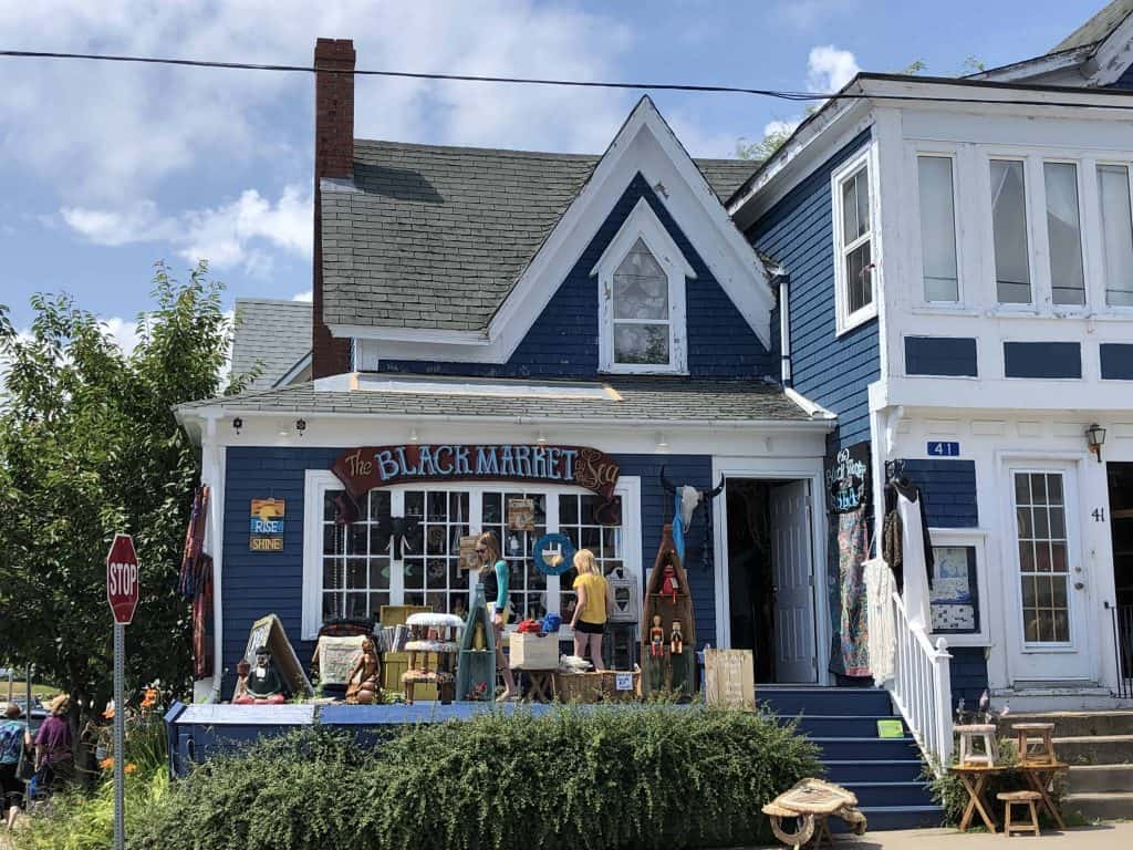 blue clapboard store called The Black Market by the Sea with girls browsing merchandise out front