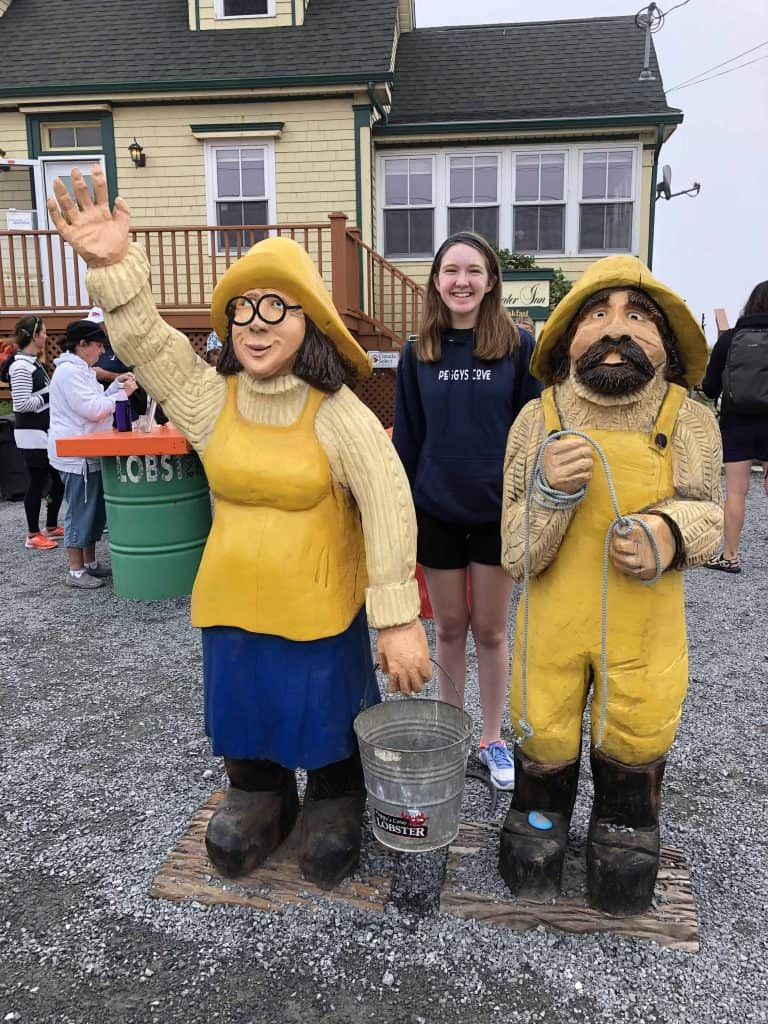 teen girls with wooden figurines of male and female fishermen in front of yellow building