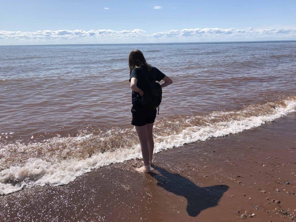teen girl standing on beach looking at ocean