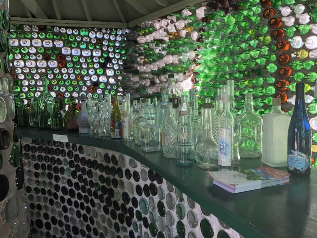 bar with empty bottles inside house made of bottles