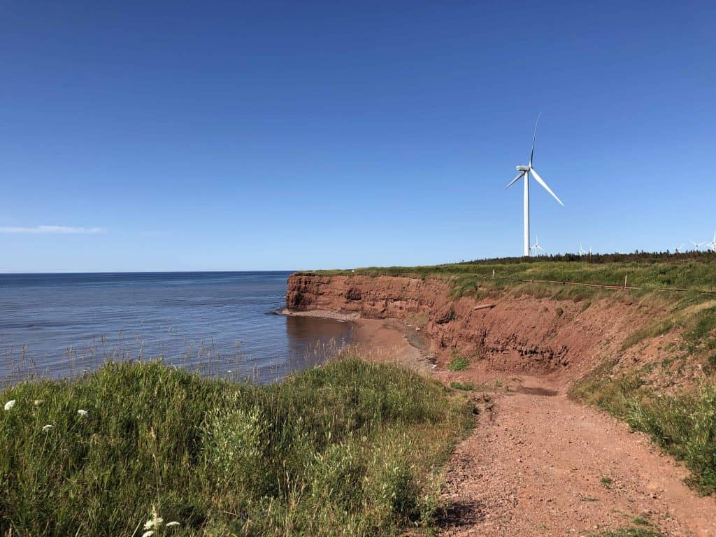 windmills along coast line with red sand cliffs - prince edward island north cape coastal drive