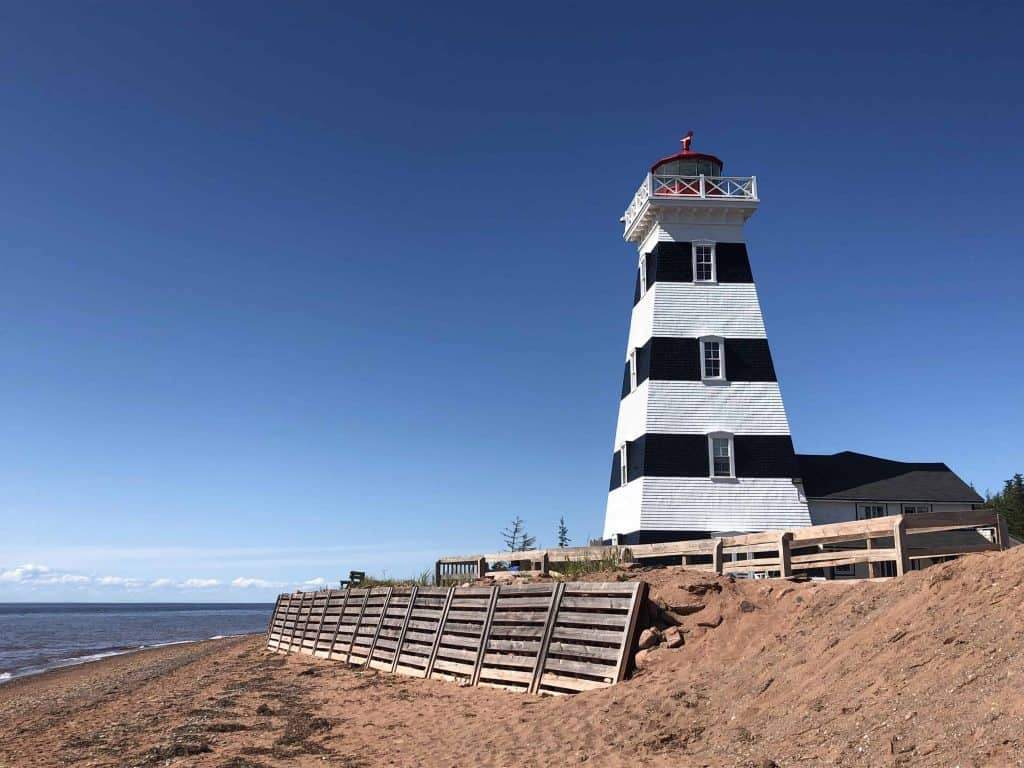 Black and white striped lighthouse on beach by ocean - prince edward island north cape coastal drive