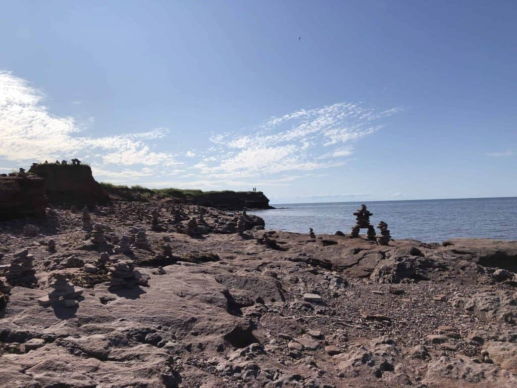inukshuks on rocky shore by ocean - north cape prince edward island