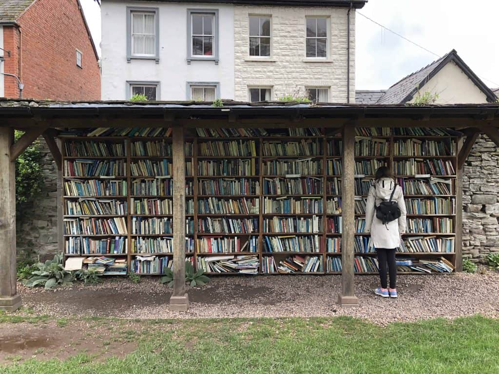 girl in front of open air book shelves in welsh village