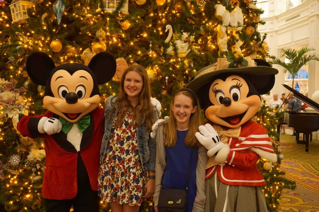 girls with Mickey and Minnie Mouse dressed in Victorian clothes in front of christmas tree