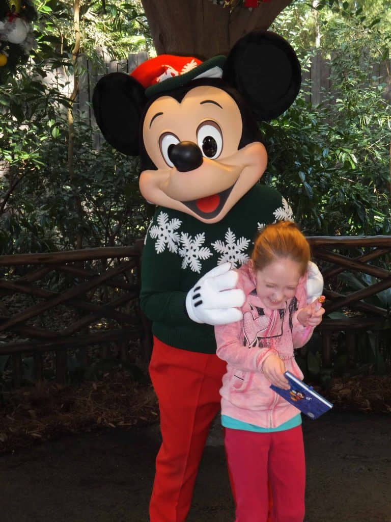 mickey mouse in red pants and green sweater tickling young girl
