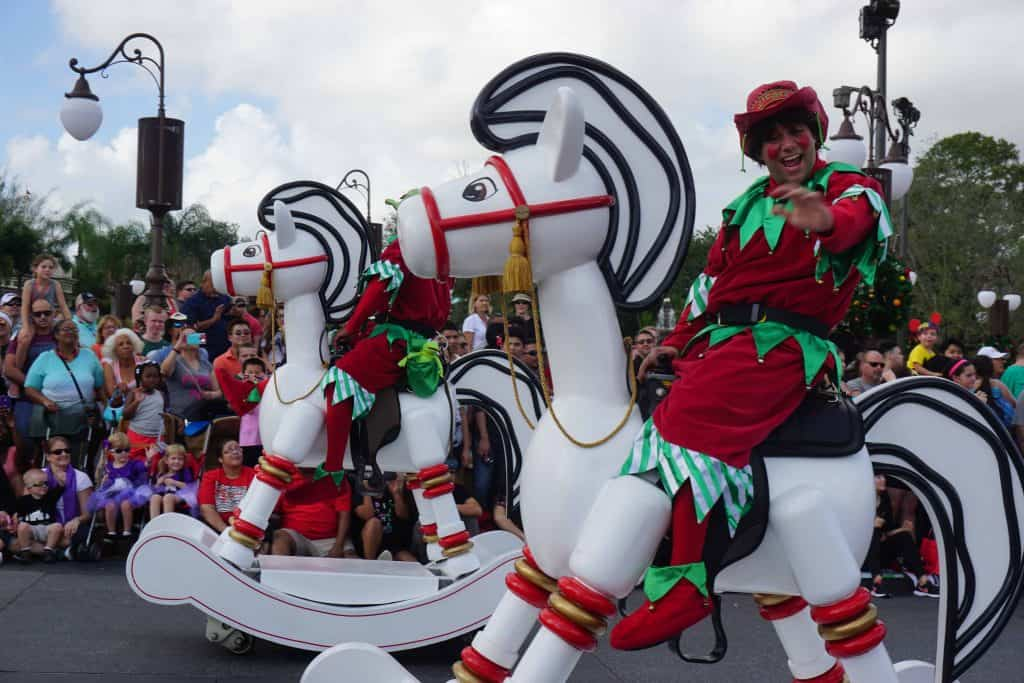 christmas characters on wooden rocking horses in disney parade