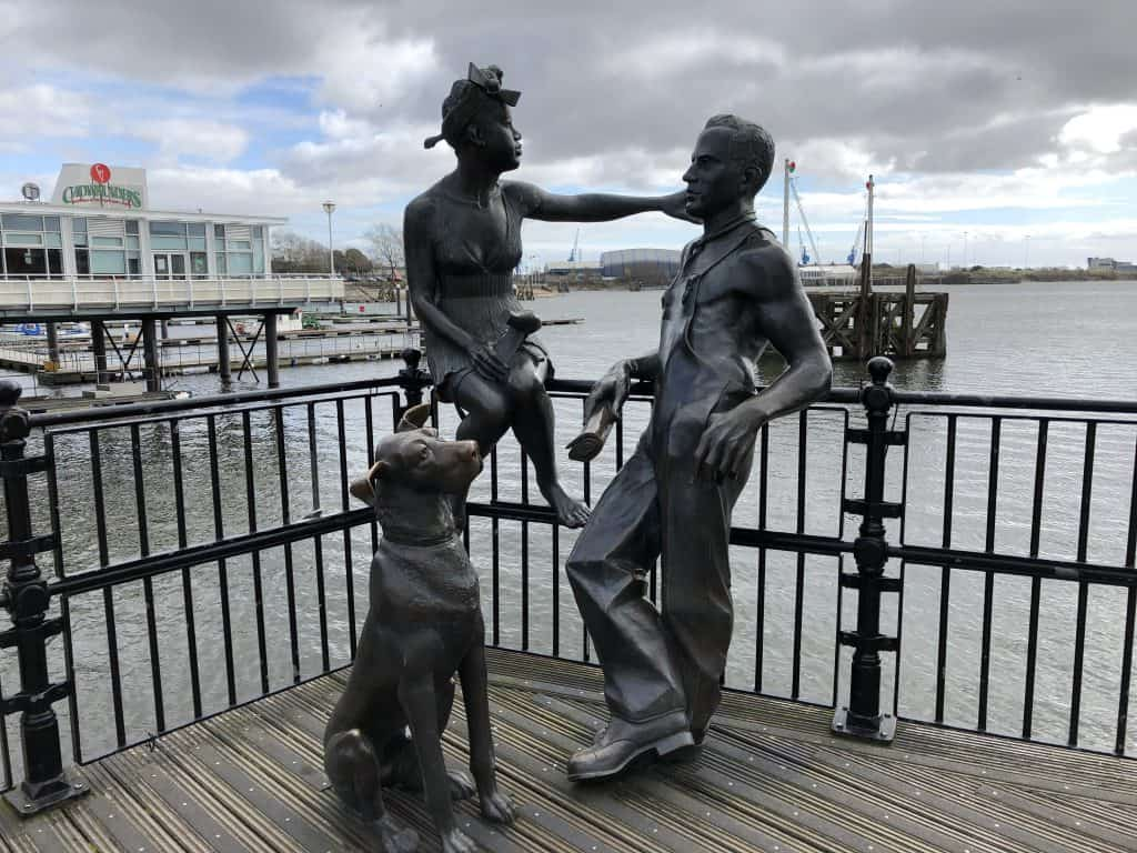 sculpture of man woman and dog on pier