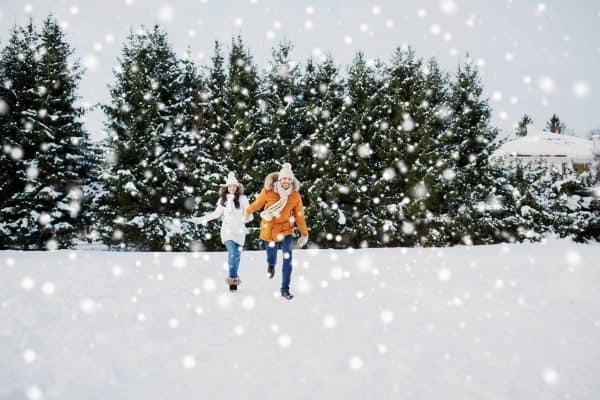 happy couple running in snow
