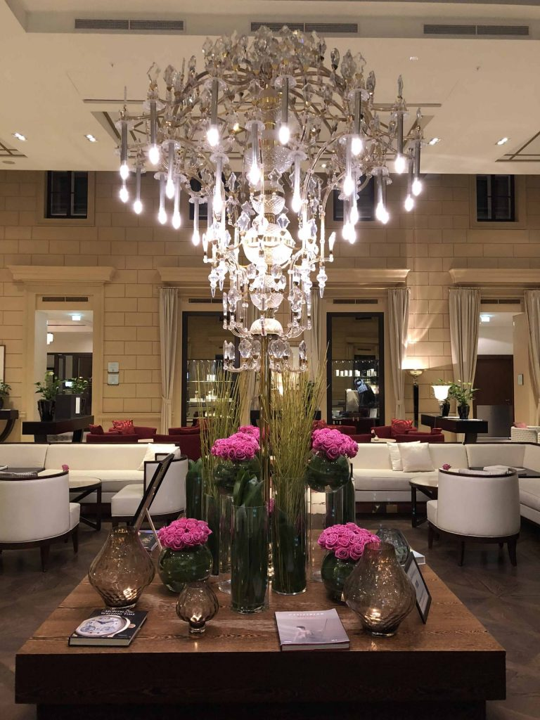 kempinski hotel vienna lobby-crystal chandelier-table vases pink flowers