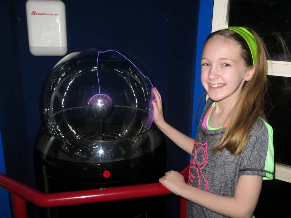 girl at ontario science centre touching plasma ball