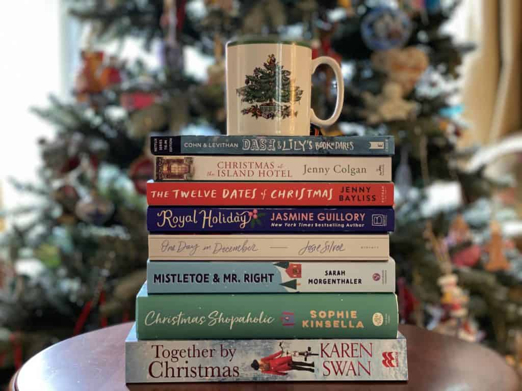 stack christmas books on table with christmas mug on top