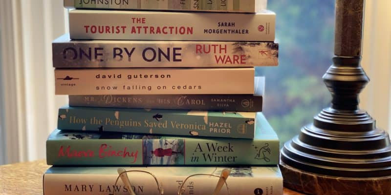 stack of books on table by lamp