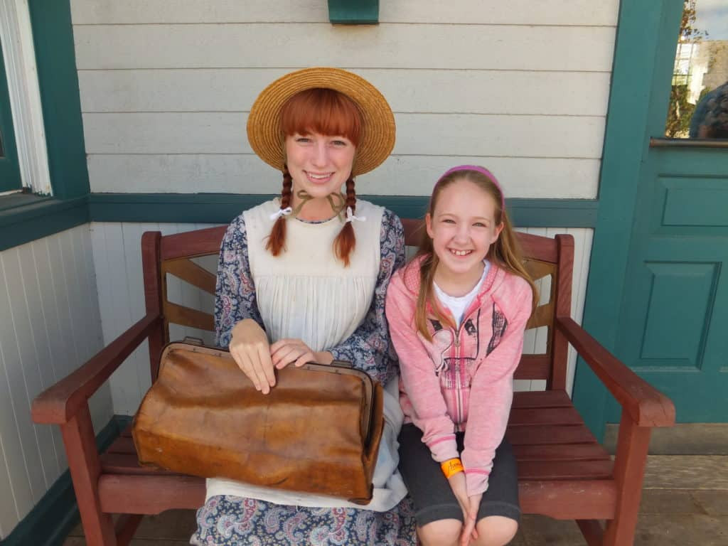 young girl sitting on bench with anne of green gables in prince edward island